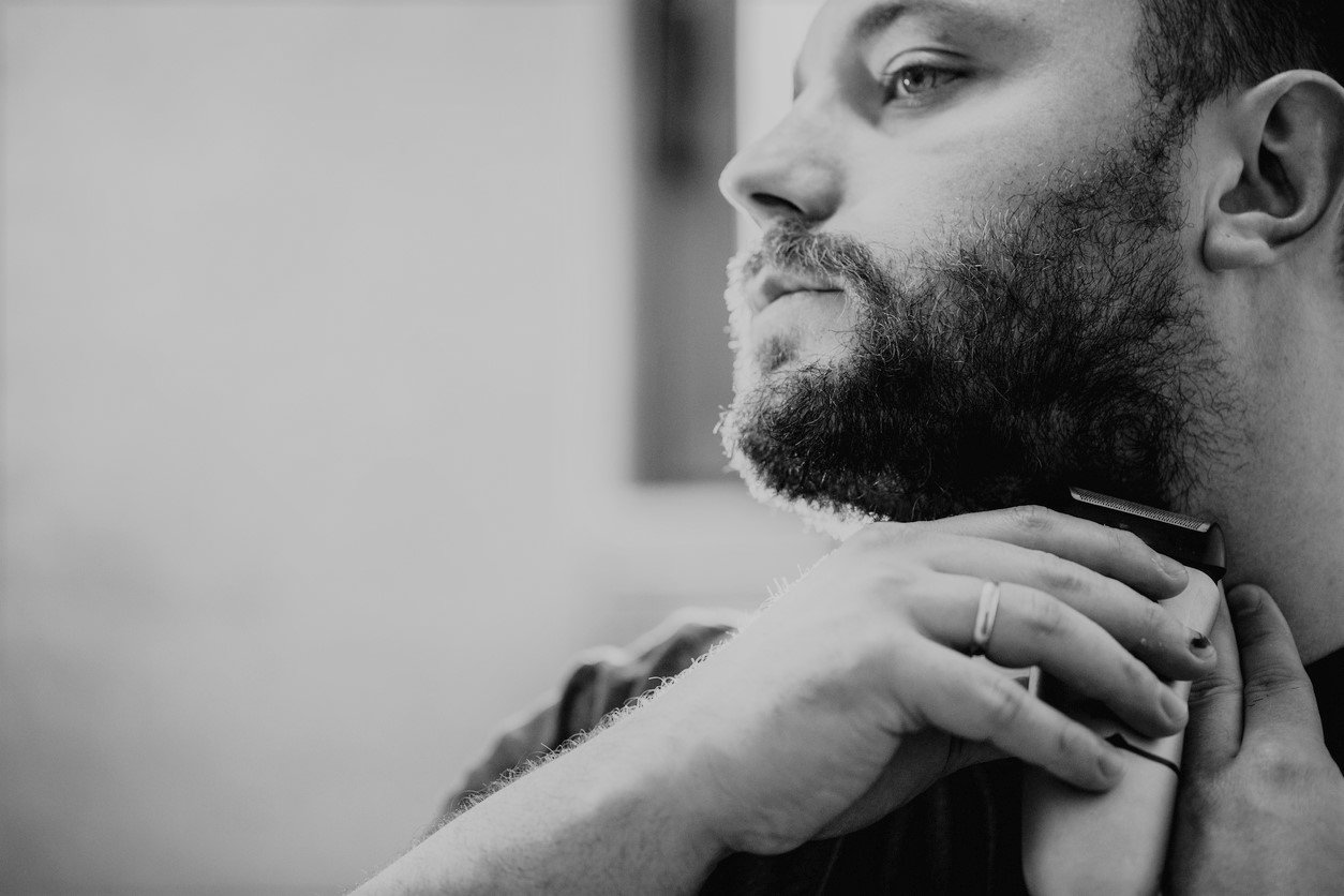 A man trimming a beard line into his neck.