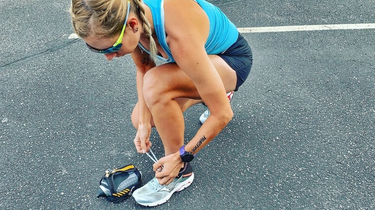 Sponsored Klean Athlete runner tying her shoelace out on the tracks.