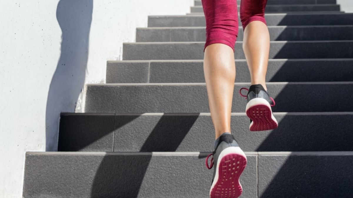 woman in workout gear walking up stairs