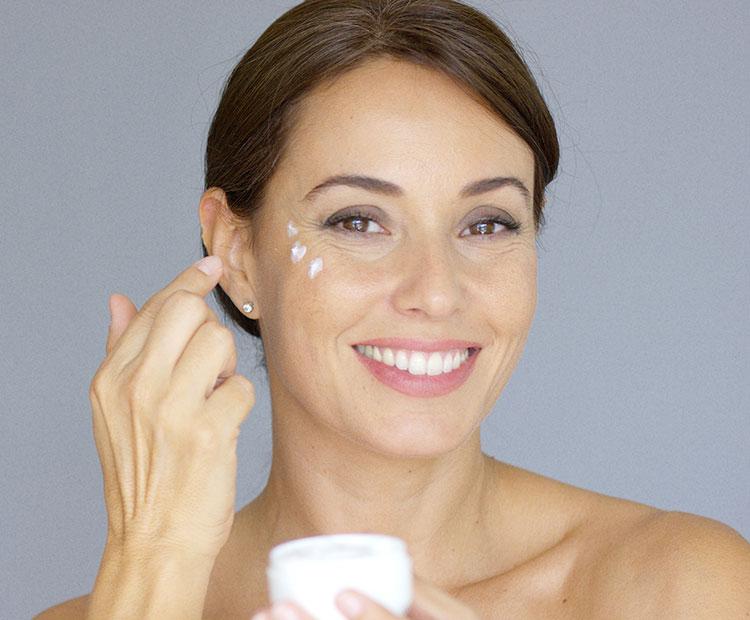 Woman applying eye cream on gray background 1
