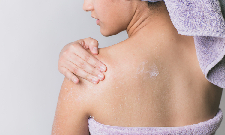 woman wrapped in towel applying lotion to shoulder