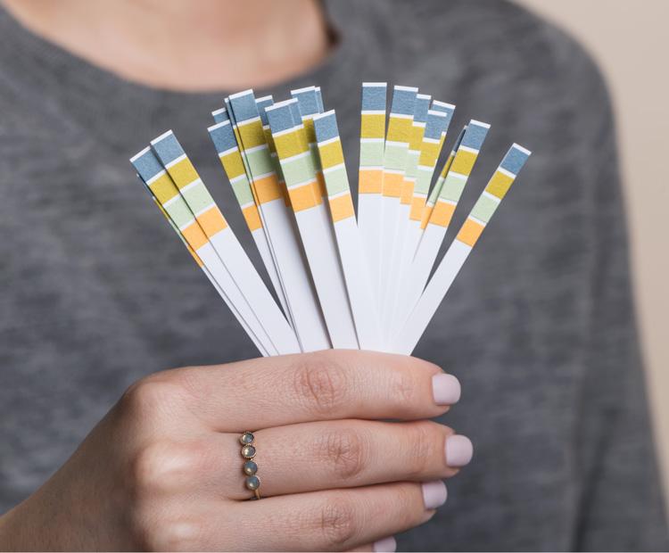 Girl holding litmus pH test strips 2
