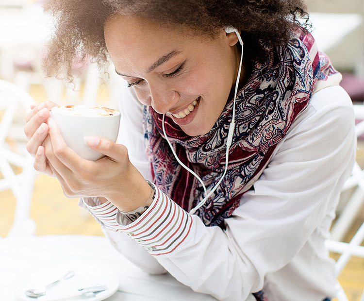 Woman-with-earphones-holding-a-cup-of-coffee-2