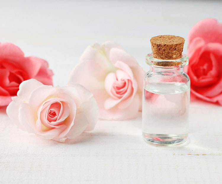 Rose-flowers-and-bottle-of-oil-on-a-white-table-2 | Dermstore Blog