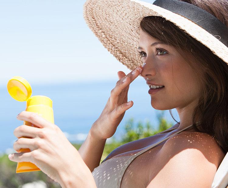 Woman-in-bikini-applying-sunscreen-on-the-face-2