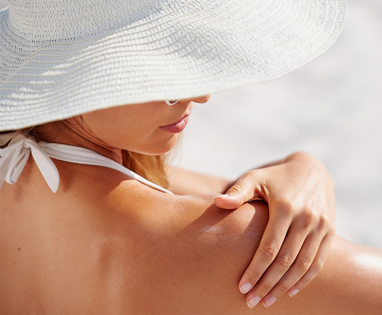 Woman-with-white-hat-applying-sunscreen-1 | Dermstore Blog