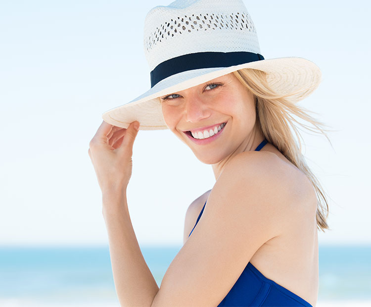 Woman on the beach wearing a white hat 1
