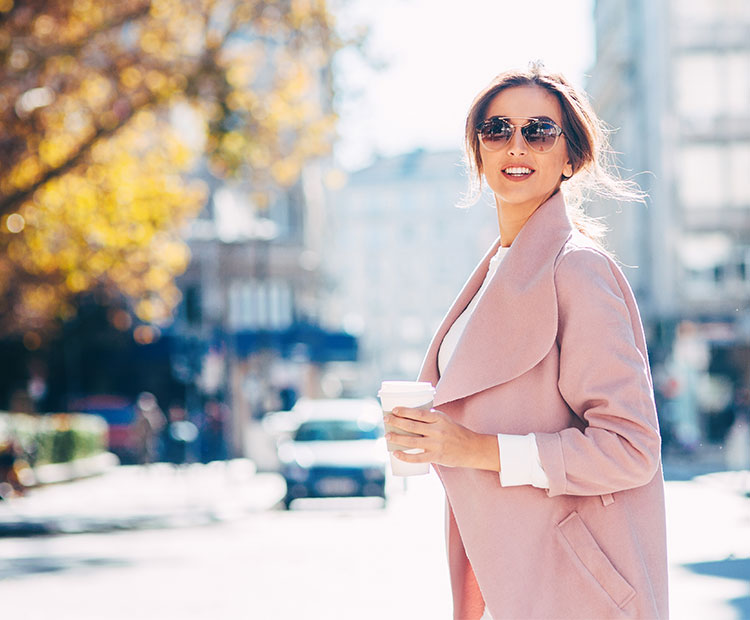 Woman in pink trench coat against fall background 2