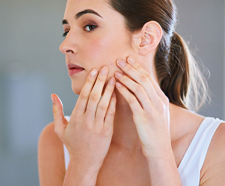 Woman touching face 1 | Dermstore Blog