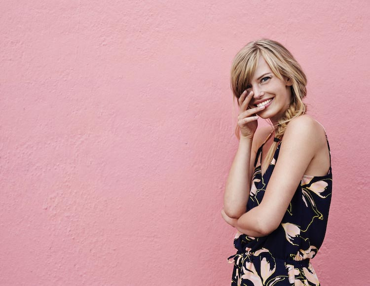 woman smiling against a pink wall