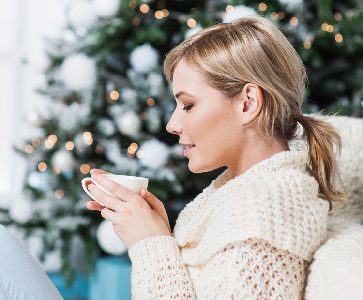 Woman sipping hot chocolate by christmas tree 1