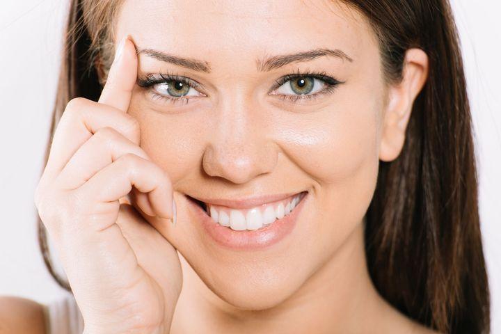 woman touching eyebrow