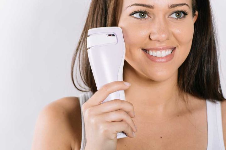 woman using a laser skin care device