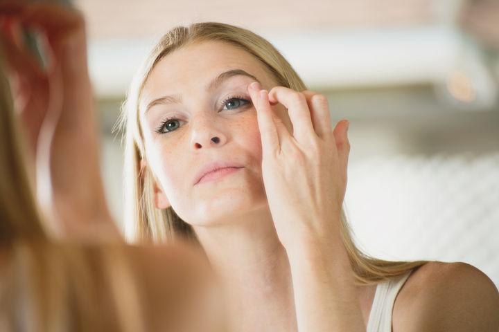 woman applying skin care around her eyes
