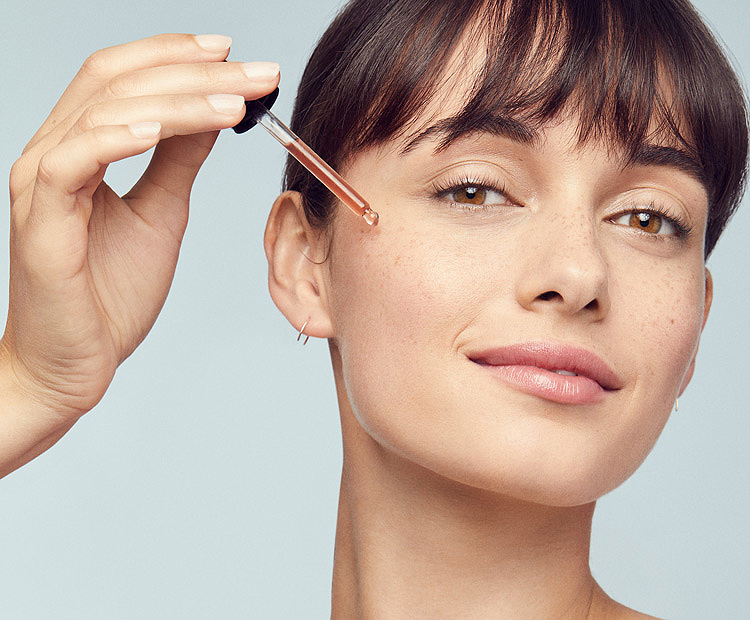 Woman applying serum on face 1