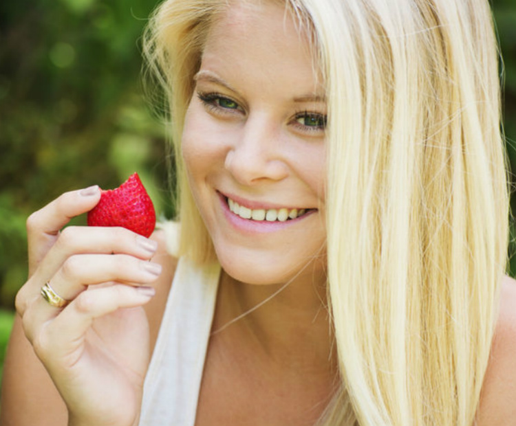 woman holding a strawberry