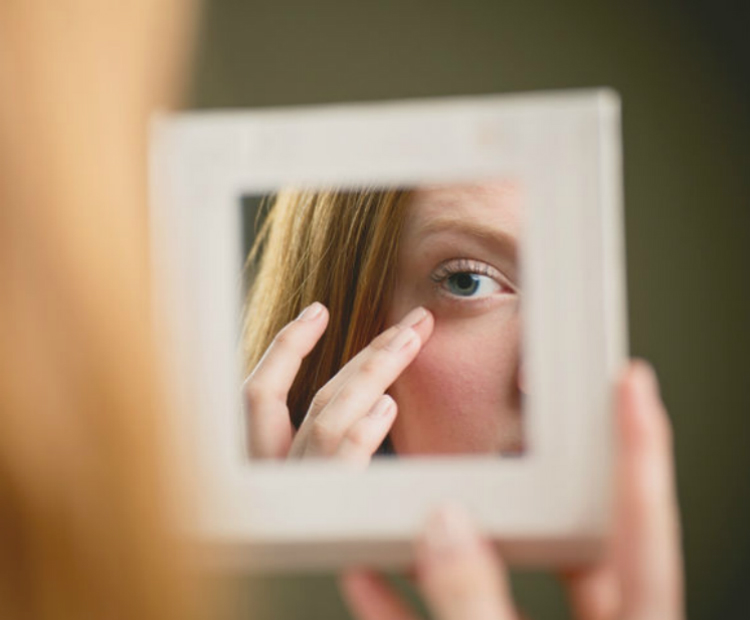 Woman checking under-eye area in mirror