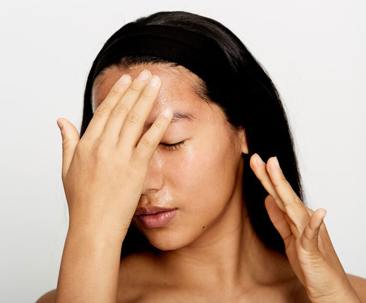 Woman applying skin care product