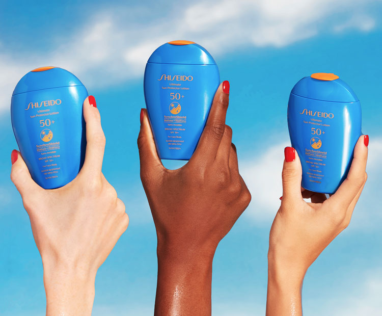 Hands holding Shiseido sunscreens