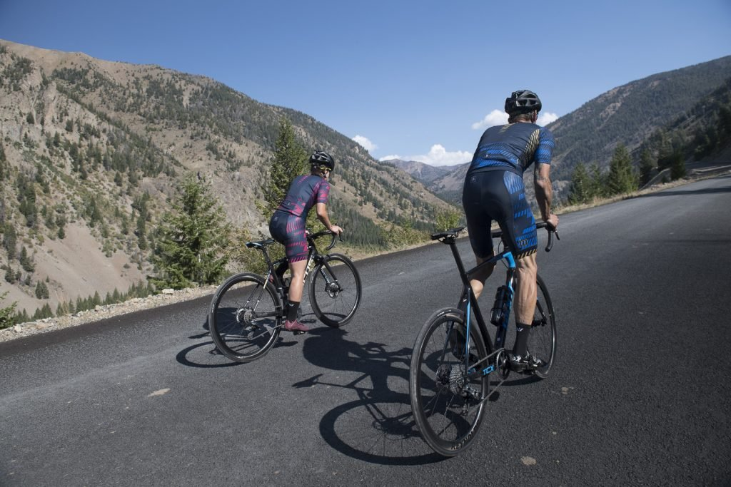 Two cyclists riding up a hill with carbon wheels