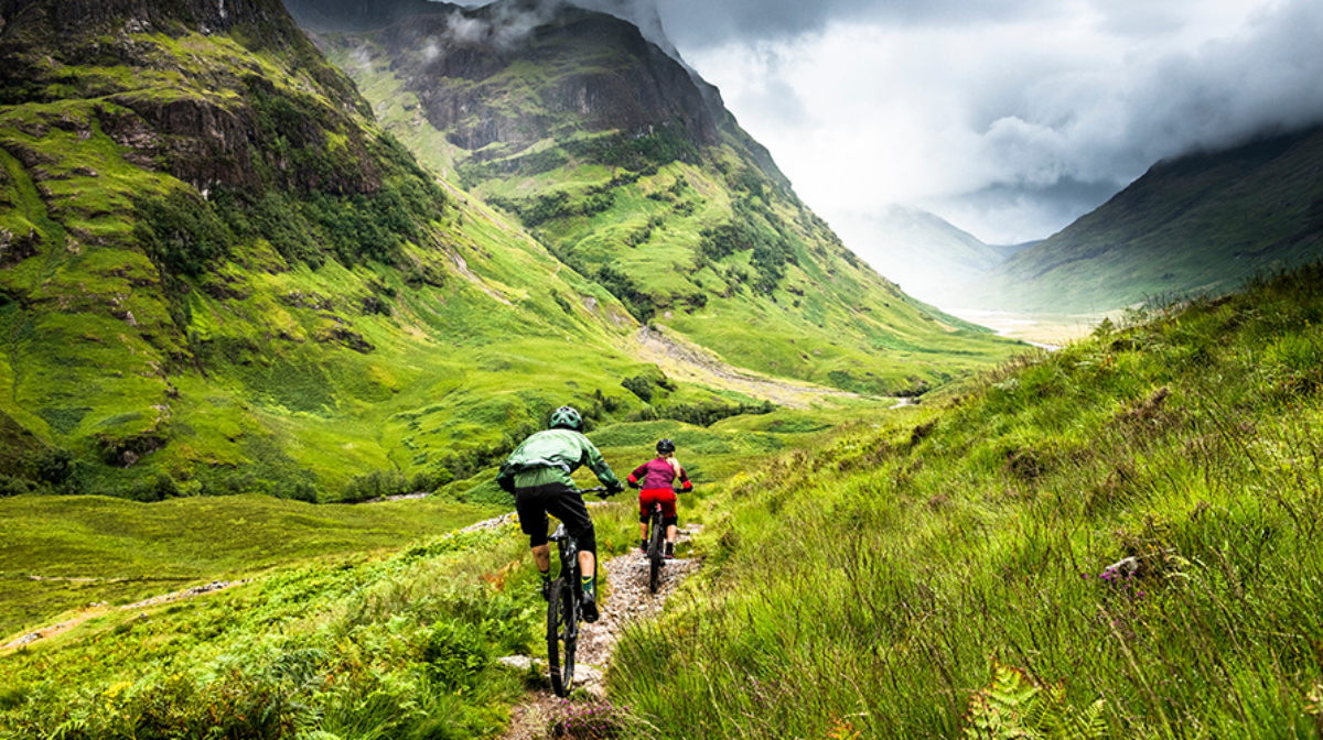Duo cycle into distance on hills