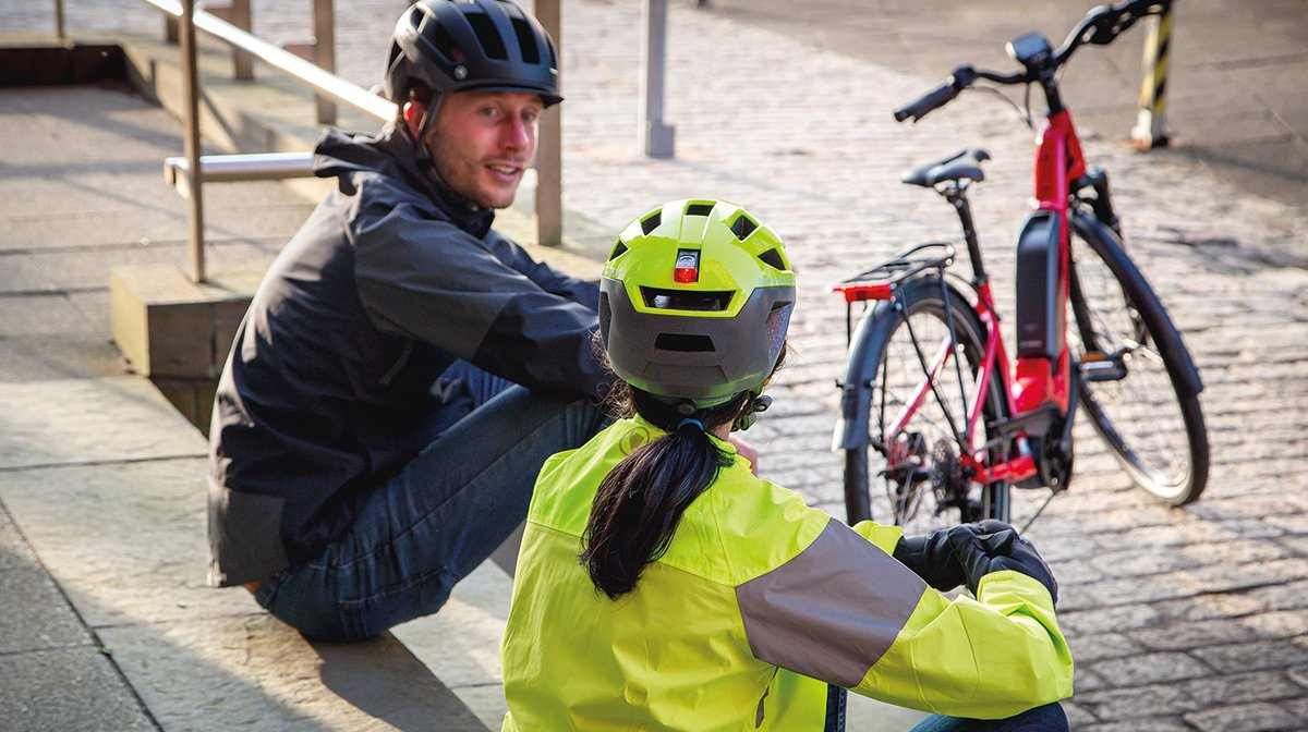 Two cyclists wearing the Urban Luminite Helmet and the Pisspot Reflective Helmet