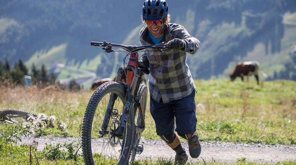 cyclist pushing bike up hill