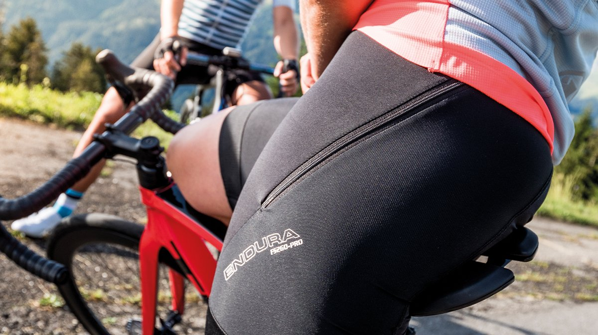 person in bicycle shorts resting on bike