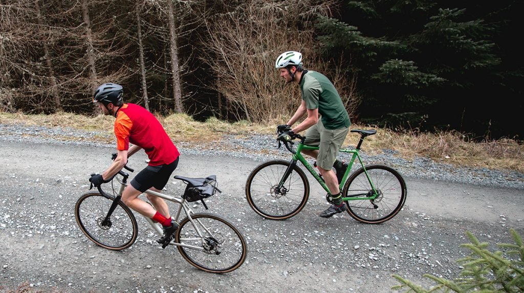 Two mountain bikers travel along a road