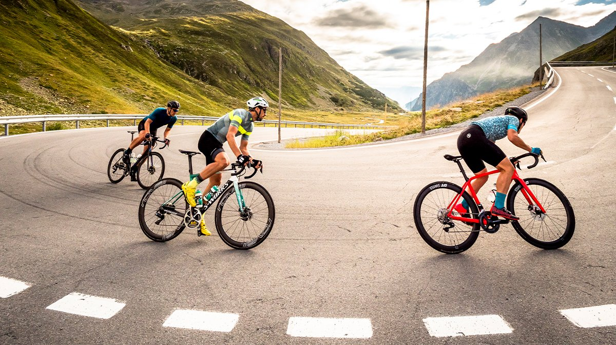 Trio of cyclists travel up steep corner