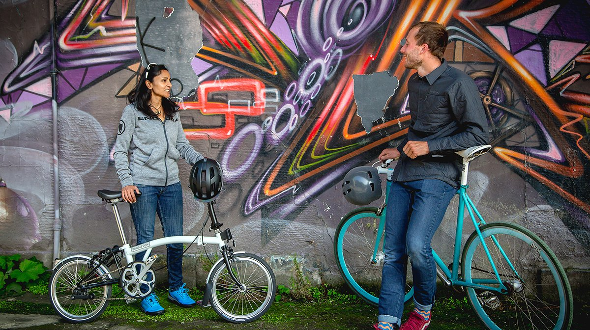 Two people lean on bikes and chat