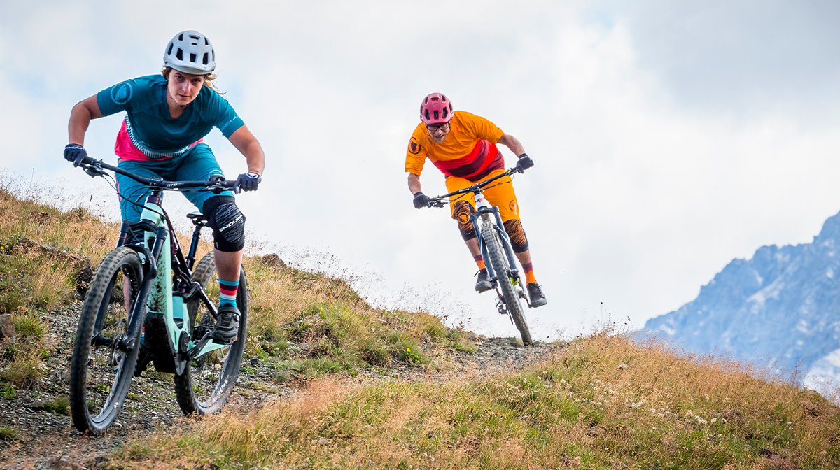 Two riders head downhill at pace
