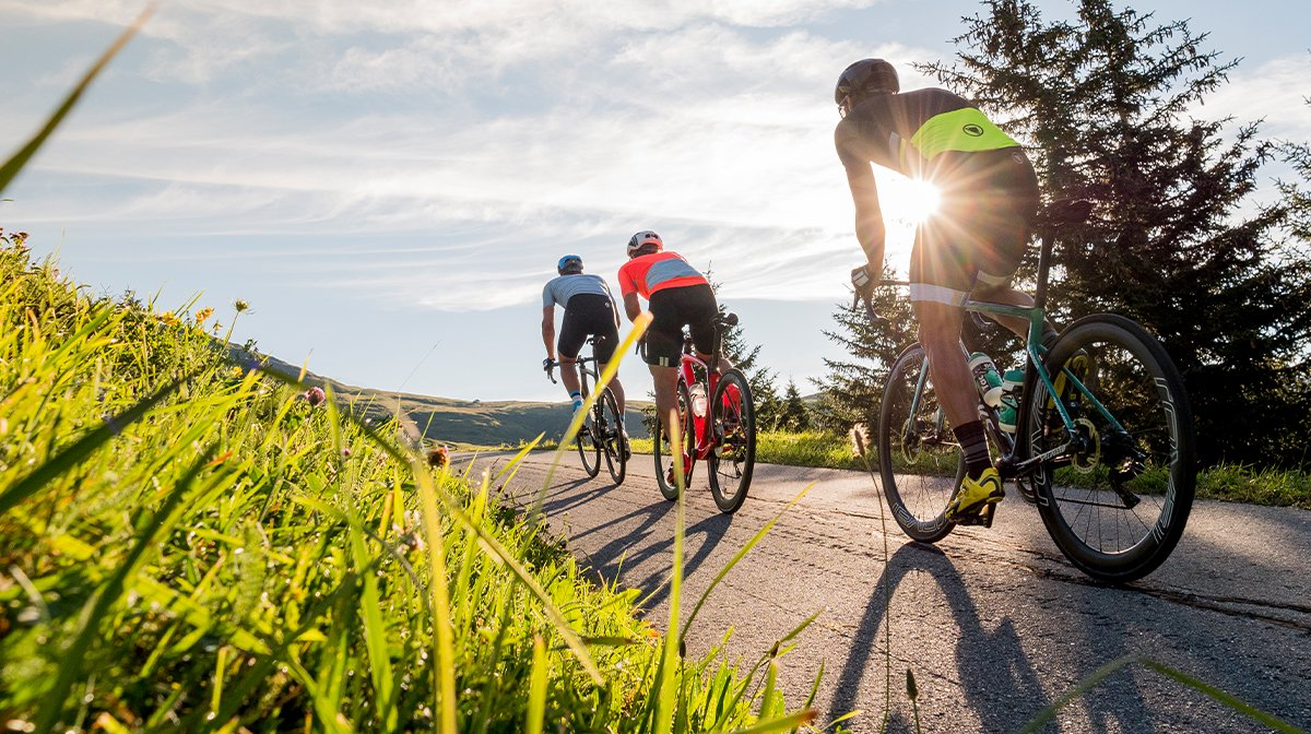 Three cyclists head into the sunset