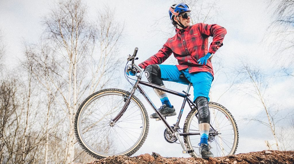 Man poses on top of bicycle