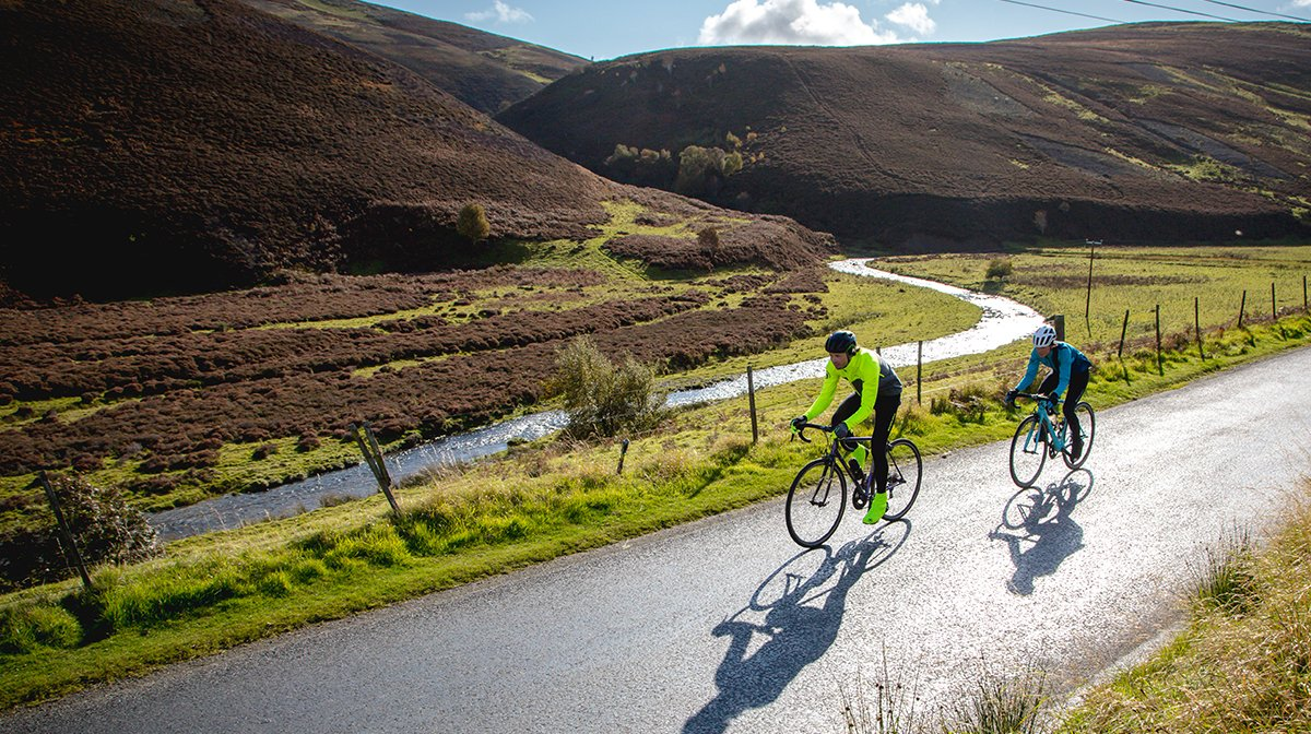 Two cyclists head down sunny road