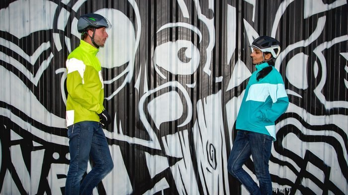 Cyclists talk infront of wall