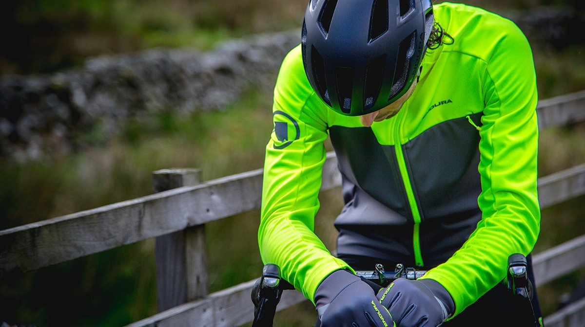 Cyclists sits on bike in yellow Endura waterproof