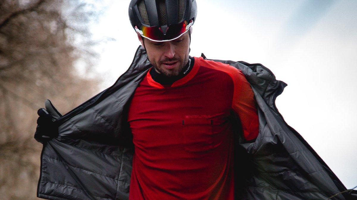 Man removes Endura black waterproof for red Endura t-shirt