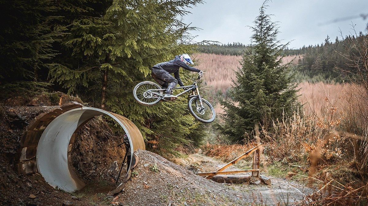 Endura rider mid jump between roads in grassy hills