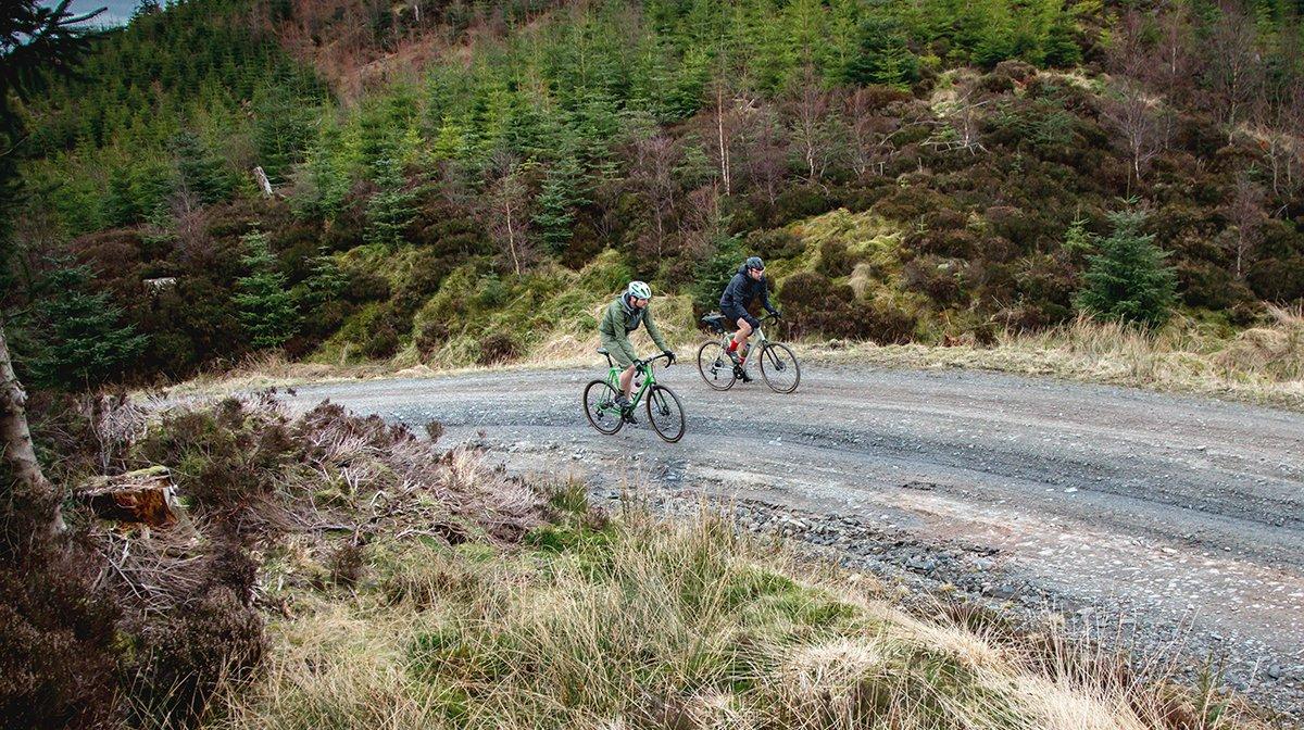 Two Endura cyclists head down gravel road dressed in Endura gear