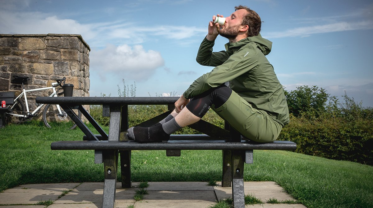 Man drinks coffee sat on Bench in Green Endura waterproof