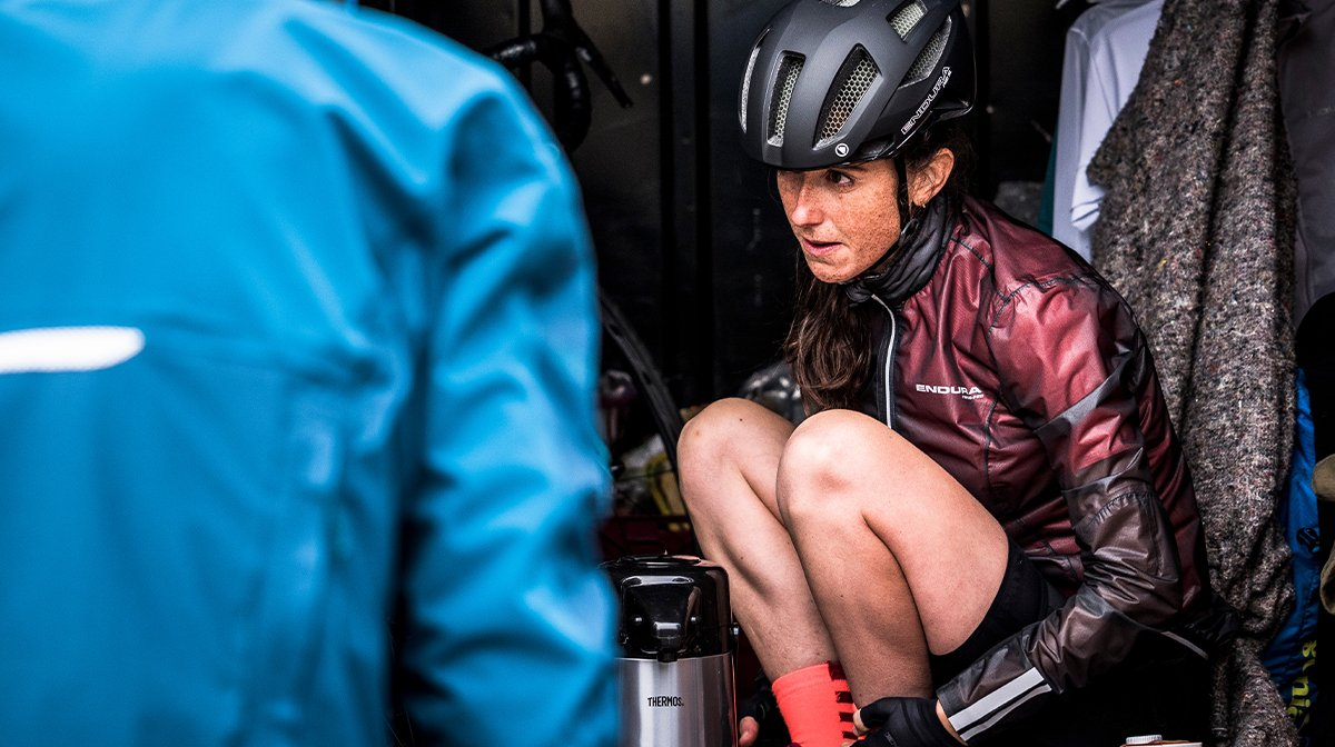 Woman sits out of the way of the rain in Endura helmets and Endura jacket