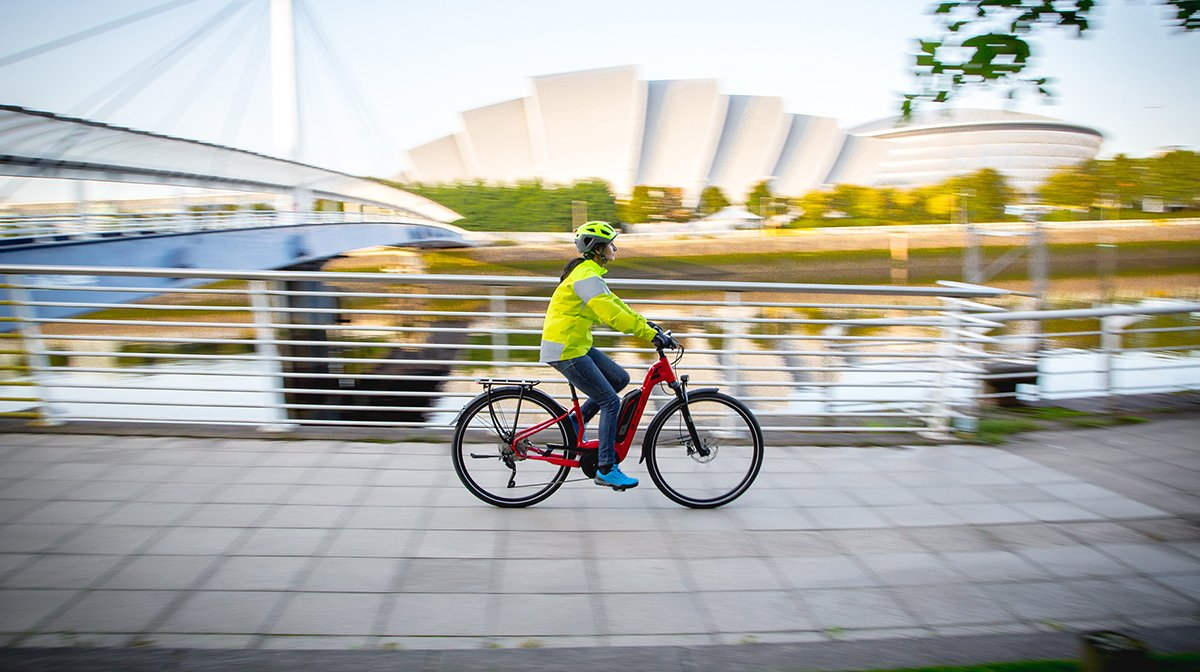 Woman cycles along quayside from left to right