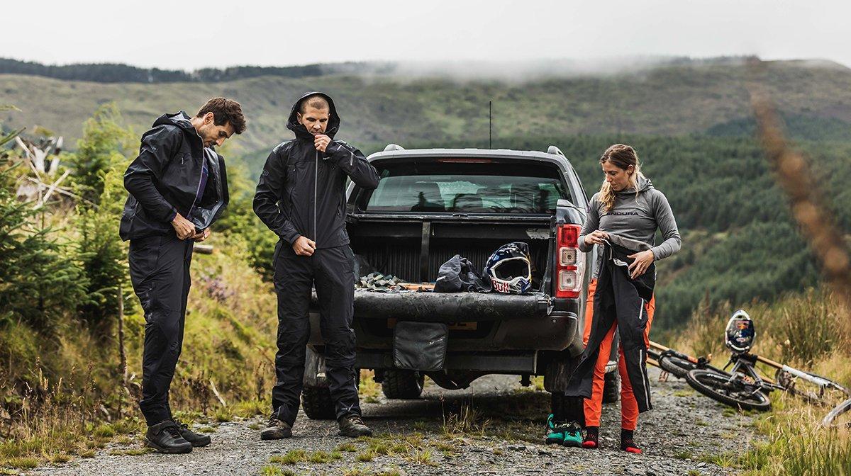 Team putting on Endura jackets in grassy hillside