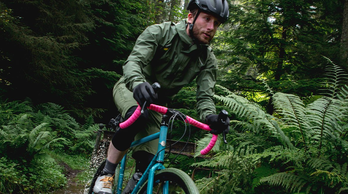 Man cycles through forest in Endura waterproof