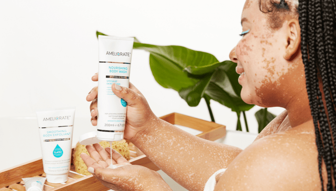 woman squeezing ameliorate nourishing body wash into hand