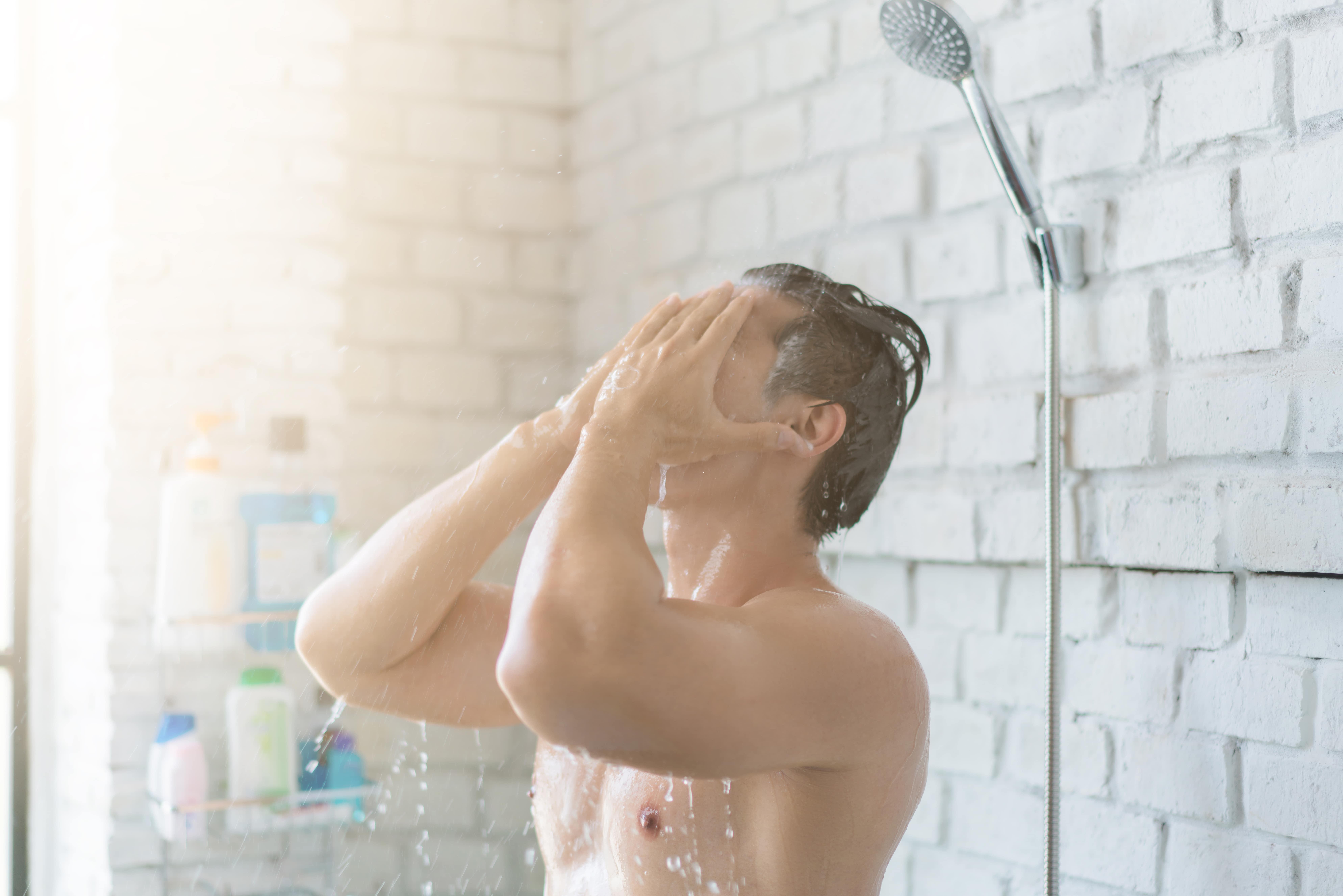 man applying conditioner in shower