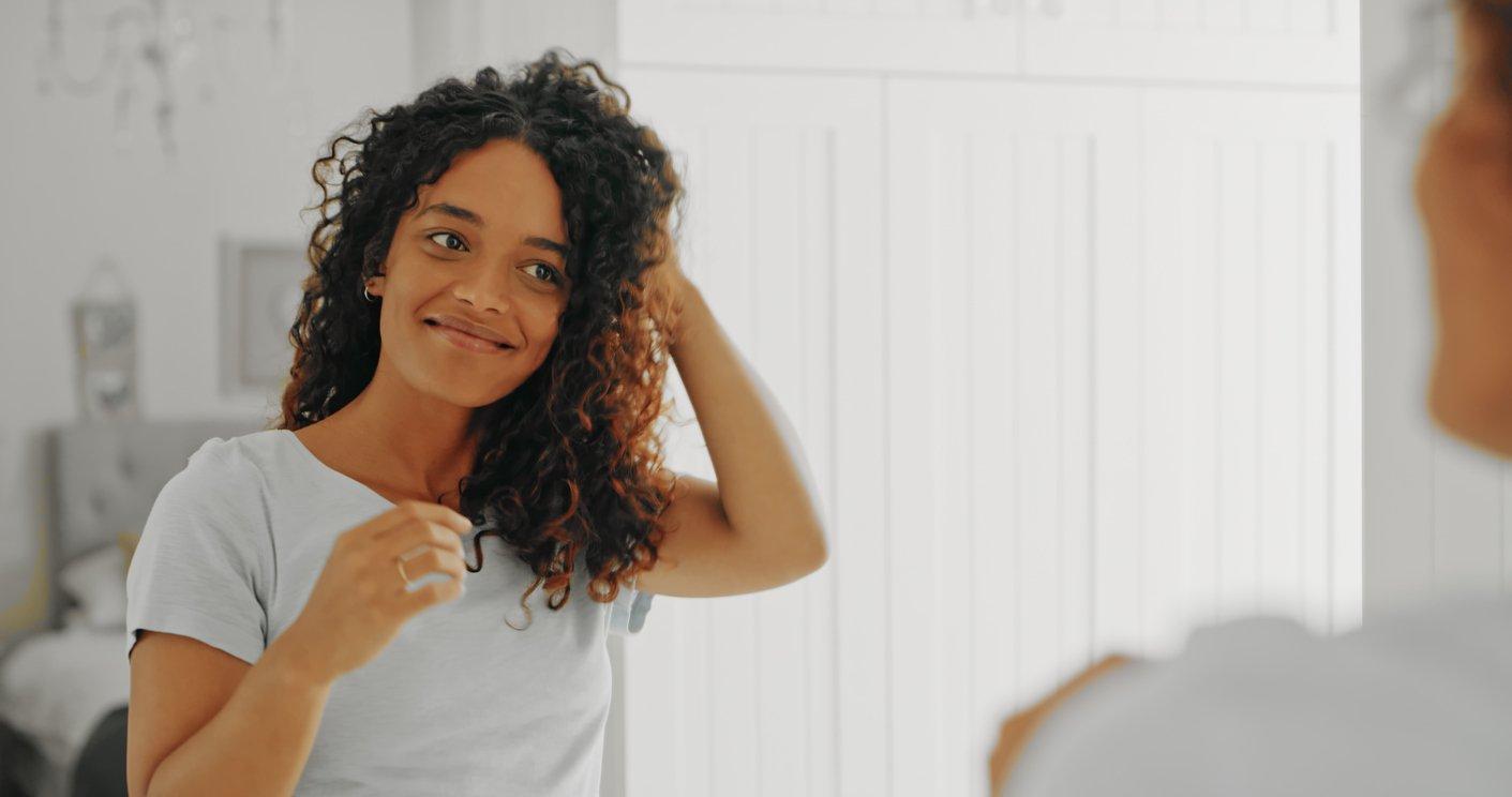 woman looking in mirror admiring hair