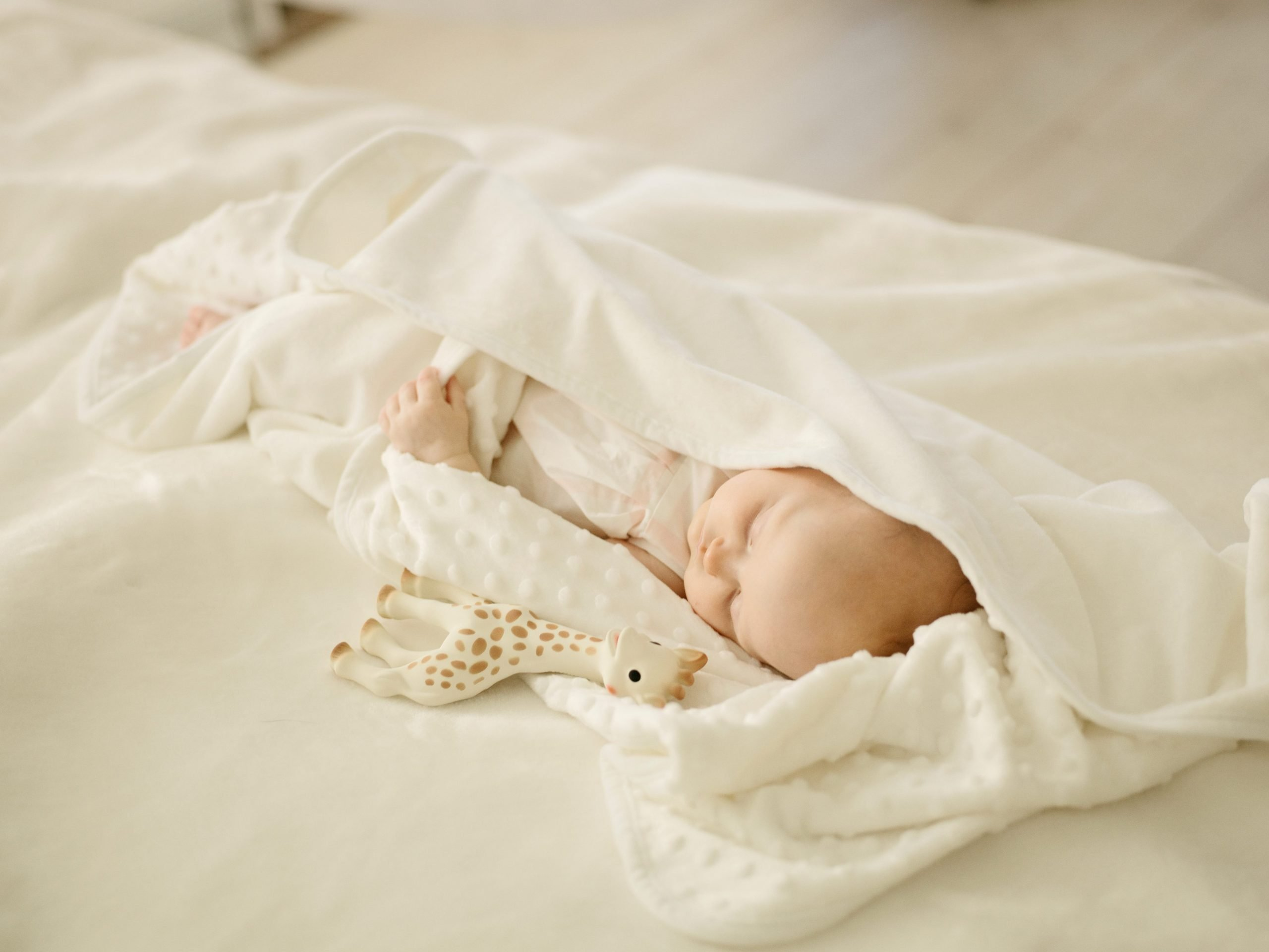 Scandinavian Baby Brands baby sleeping with toy