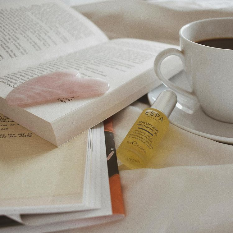book, coffee and facial serum on a bed